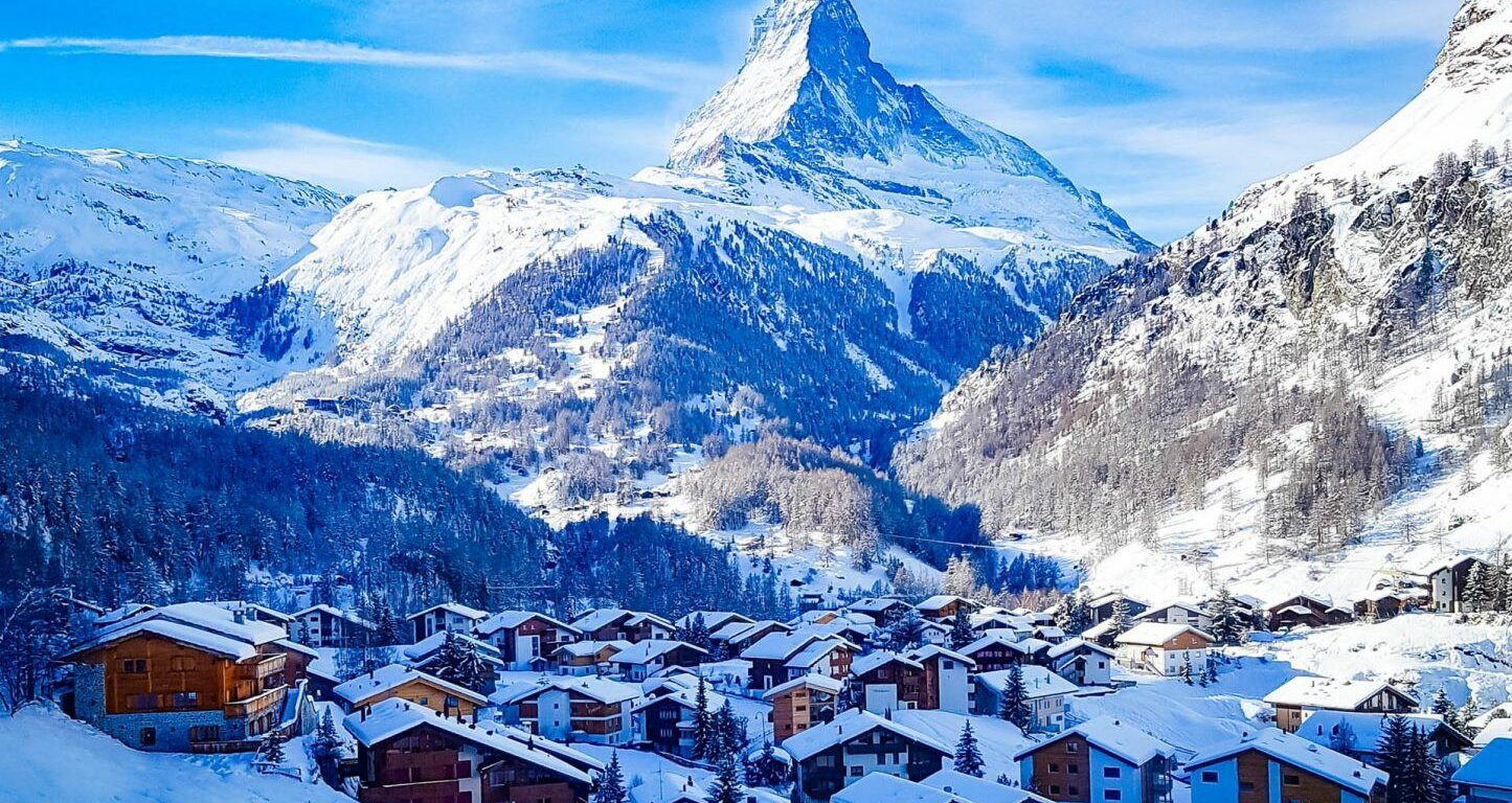 View of the Matterhorn Switzerland with snow covered homes at the forefront and base and misty blue skies in the background.