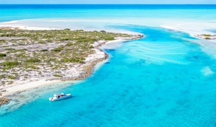 Crystal clear blue lagoon dotted by a lone chartered boat