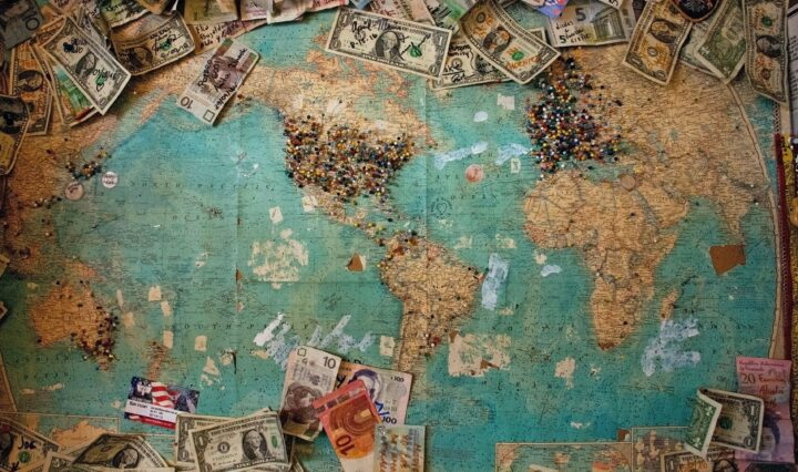 Picture of a world map with money of differnt currencies around it.