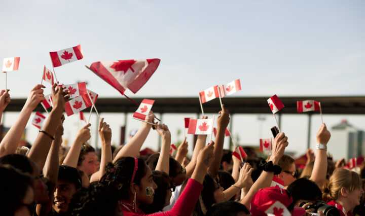 People waving Canadian flags on Canada Day