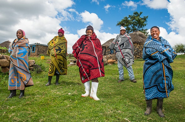 Foru basotho people of both sexes standing in the Basotho tribal blanket in front of hut on green grass