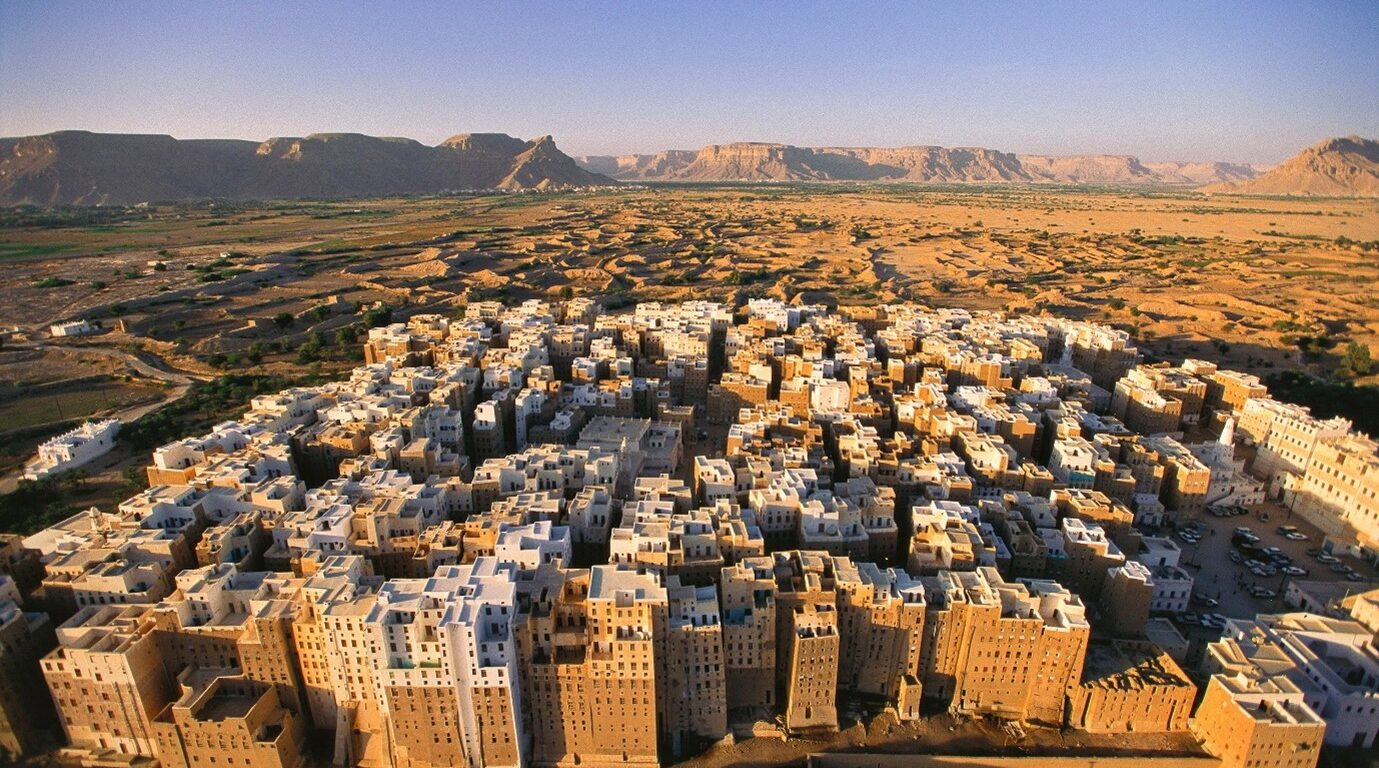 The mubrick skyscraper city of shibam in the middle of the desert with the sun setting