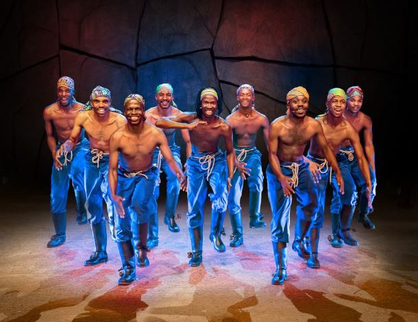Gumboot dancing troupe on stage in blue overalls and do-rags without shirt