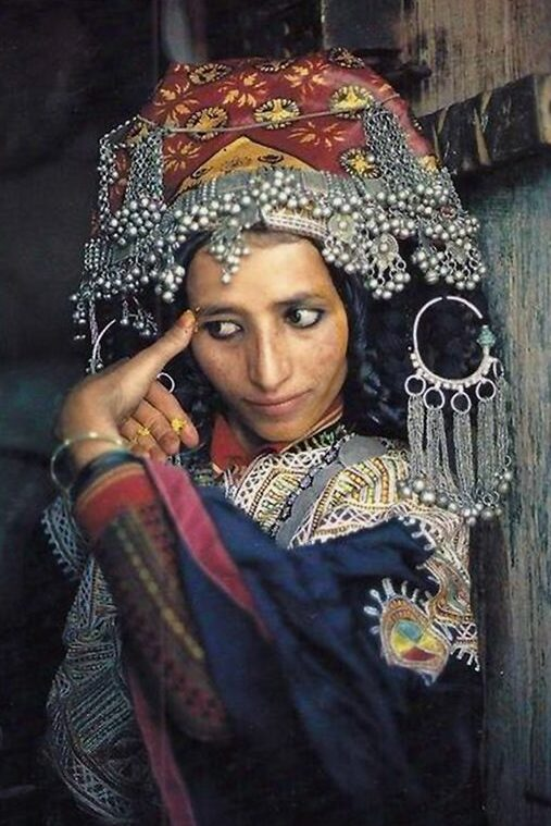 A yemeni woman applying tumeric make up with a big headdress and plenty of silver jewellry in a doorway in a village
