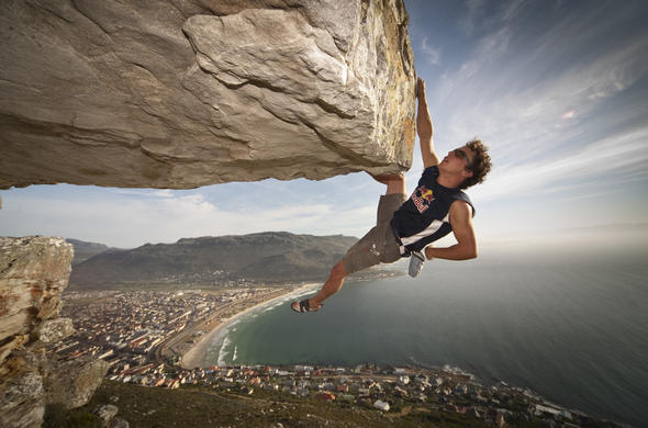 Man hanging with one hand from a cliff over cape town in his rock climbing clothes