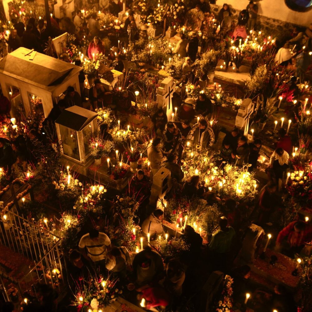 An aerial view of the grave yard in Mexico lit with candles, surrounded by flower arrangements and people praying for the souls of the departed late at night.