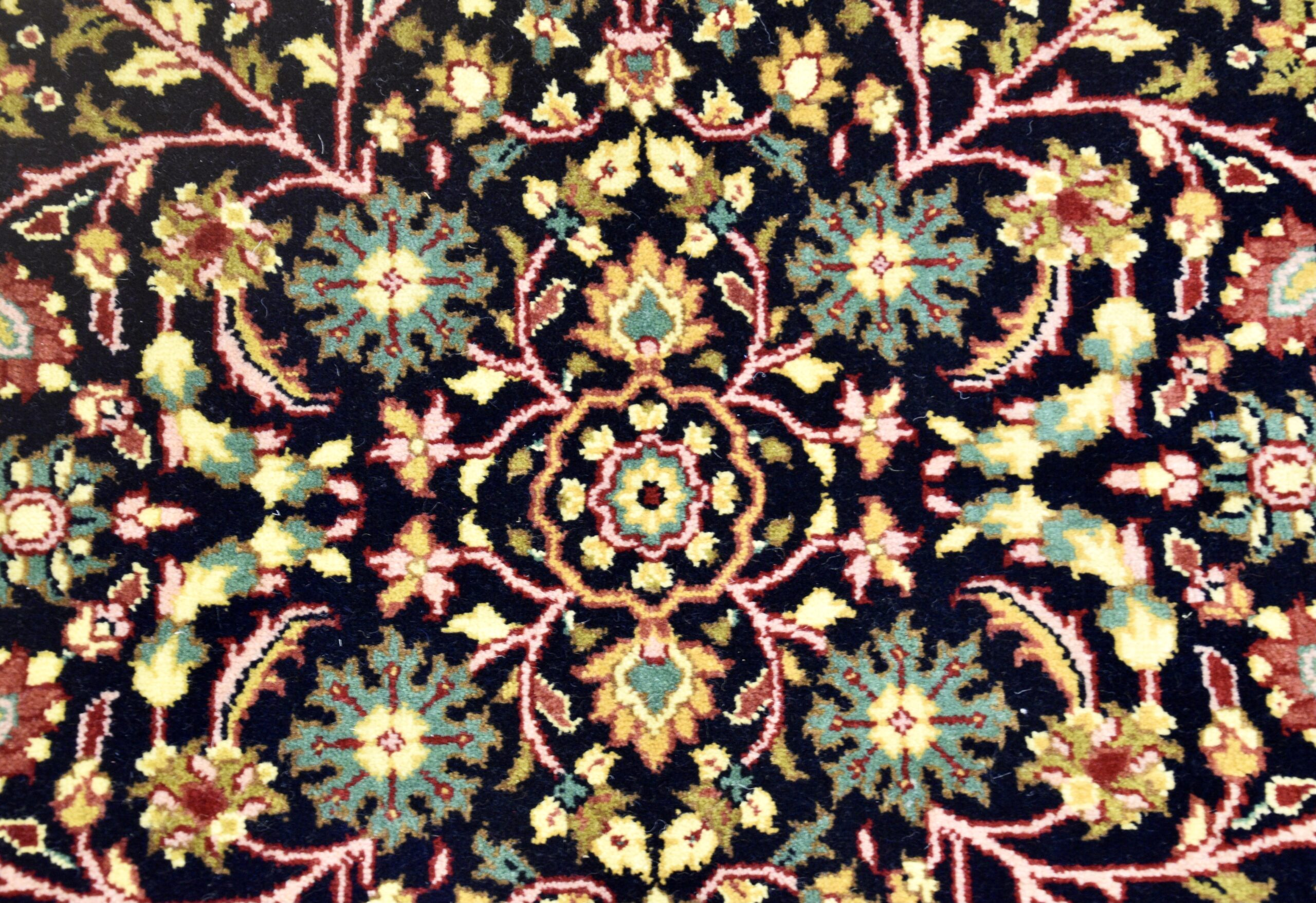 Up close of a Turkish rug with floral patterns in teal, orange, pink,and yellow on a black background.