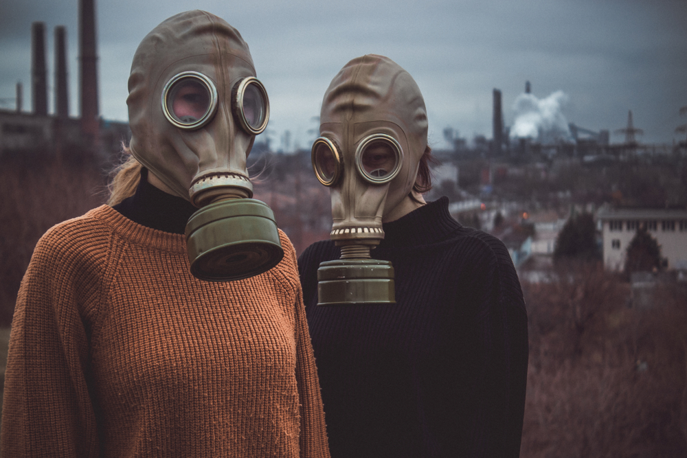 Two people wearing gas masks stand in front of a blurred city outline with a gray sky