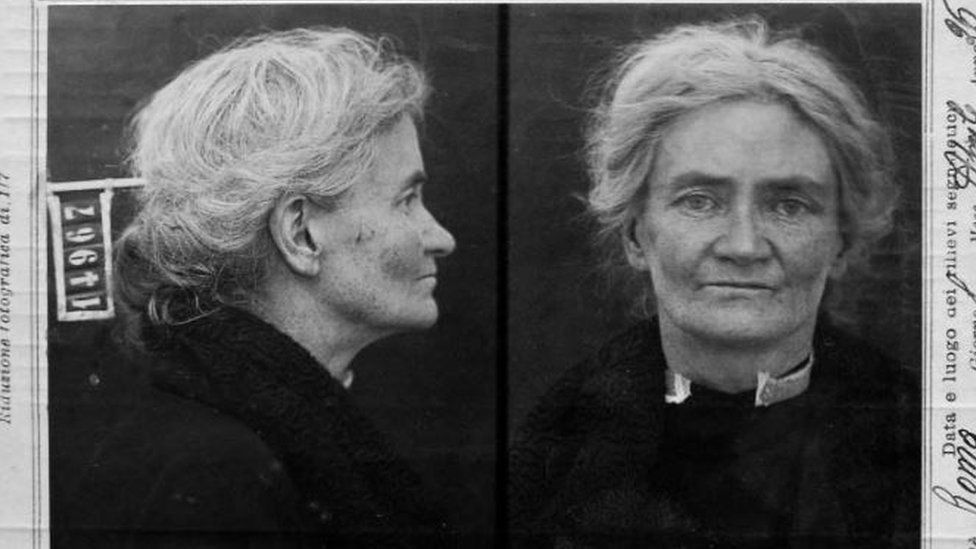 A black and white mug shot of an elderly woman with white hair braided back in both profile and front facing poses.
