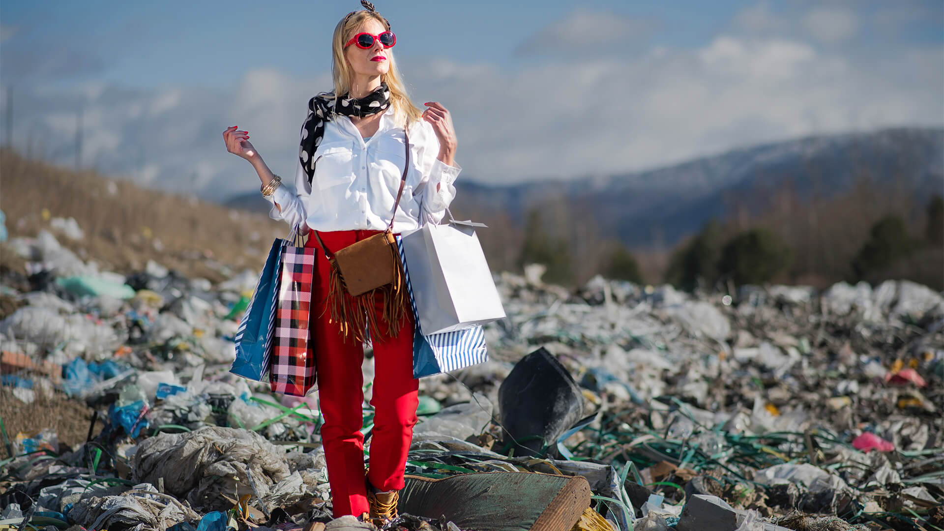 A woman holding shopping bags stands in a pile of fast fashion waste