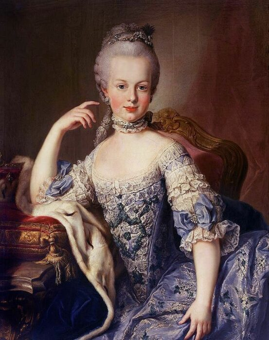 A painting of a young Marie Antoinette reclining on a low sofa wearing a gown of blue and white with her hair pulled back from her face and coiffed high upon her head.
