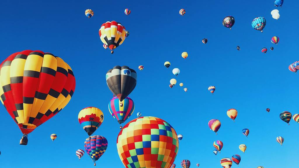 Shows a bevy of hot air balloons in flight.
