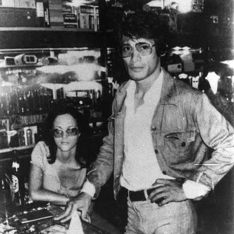 A black and white photo of sobhraj and marie in a bar, with charles standing at a table, one hand on his hip and Marie seated behind him wearing dark sunglasses.