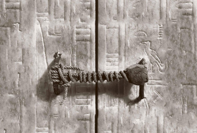 A carved off-beige door witha wooden and twine handle going across the opening, like a seal.