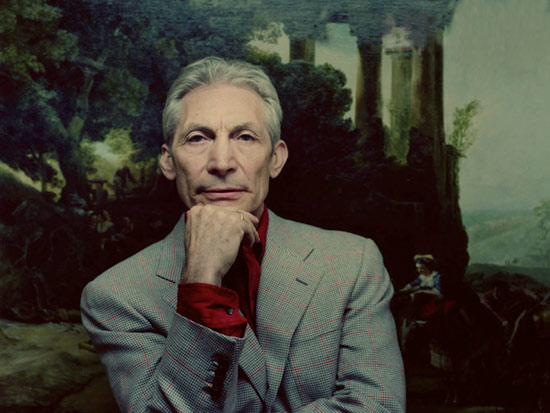 A portrait of Charlie Watts, likely taken in the 2010s. He is wearing a gray suit. A classical painting is in the background
