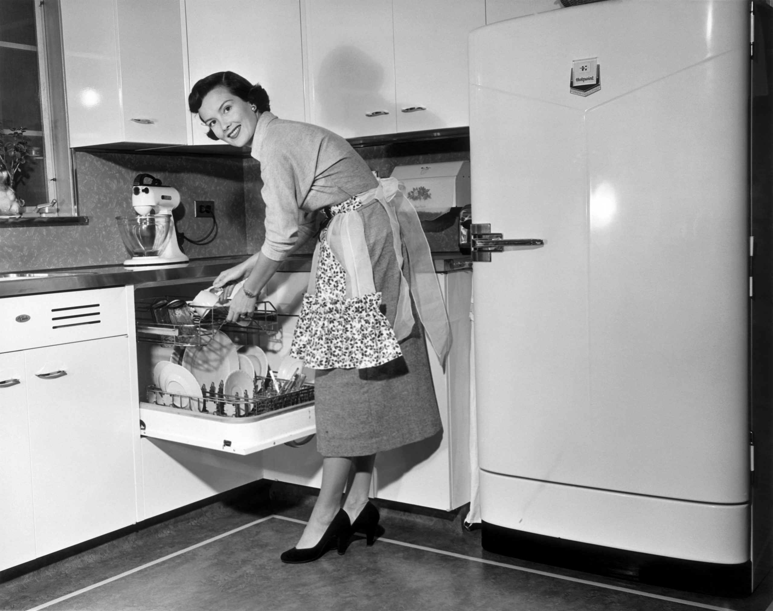 Black and white image of a 1950s woman crouching over to stack the dishwasher while smiling back at the camera