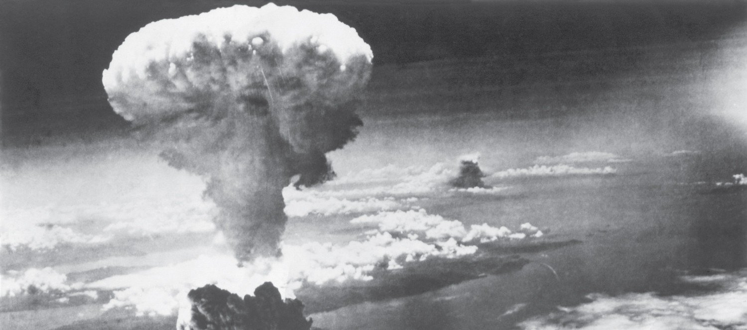 A black and white photograph of a mushroom cloud after the descent of a nuclear bomb, seen high in the sky.