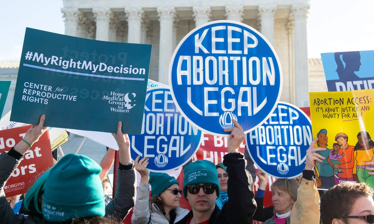 Protestors against abortion law gather and hold up blue signs that say 'keep abortion legal'