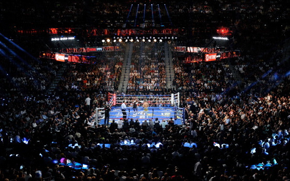 A shot of a boxing ring from the upper seats in a stadium.
