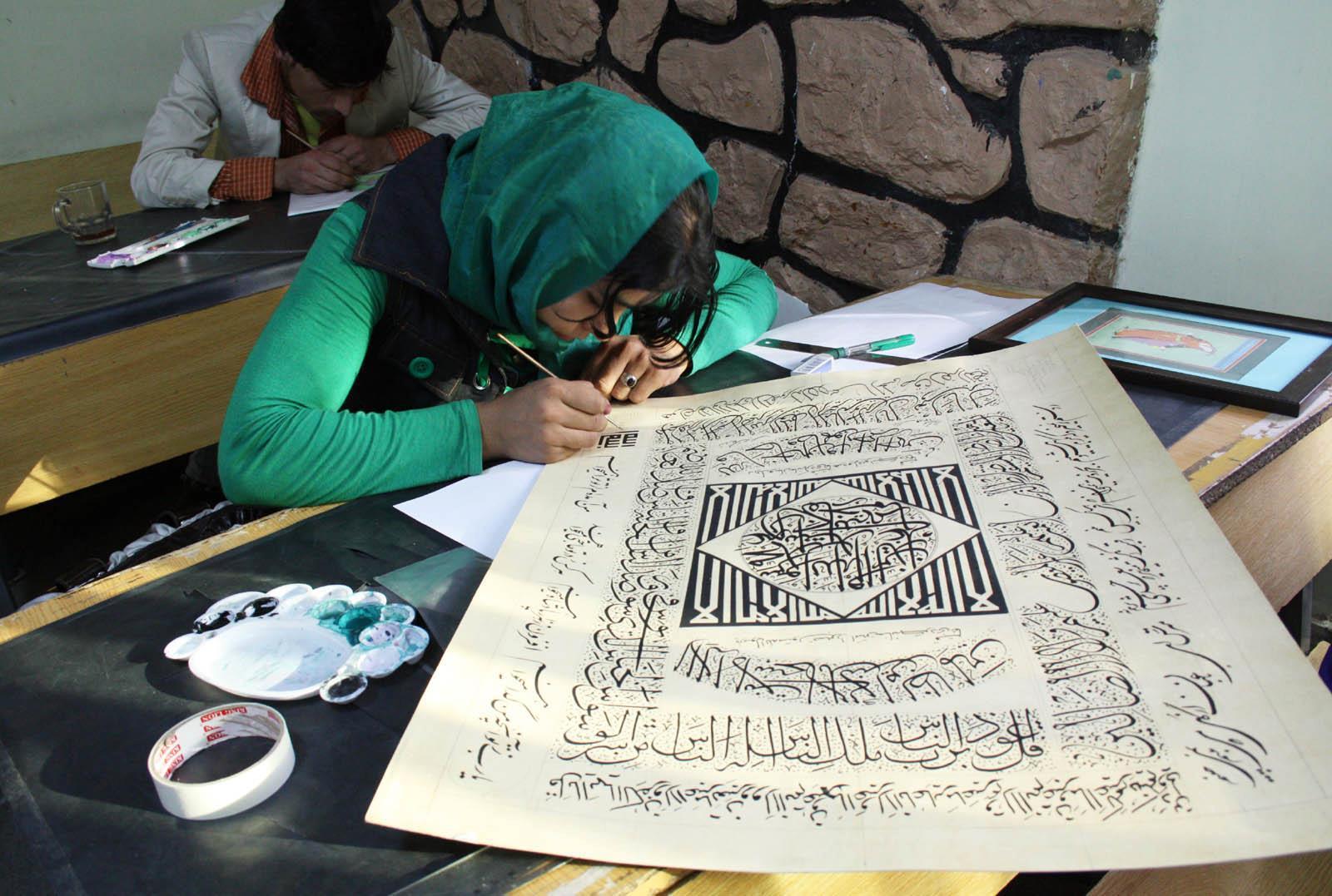 a girl working on afghan calligraphy