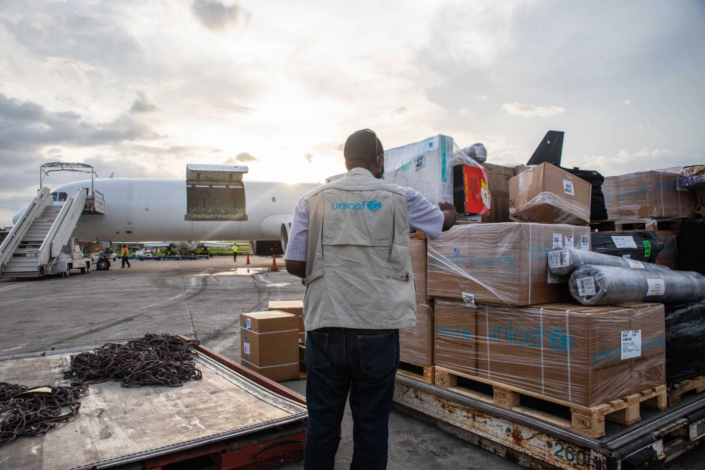 A coloured photograph pof a man standing on a landing strip with supplies provided by UNICEF for the survivors and injured of teh Haiti earthquake in 2021