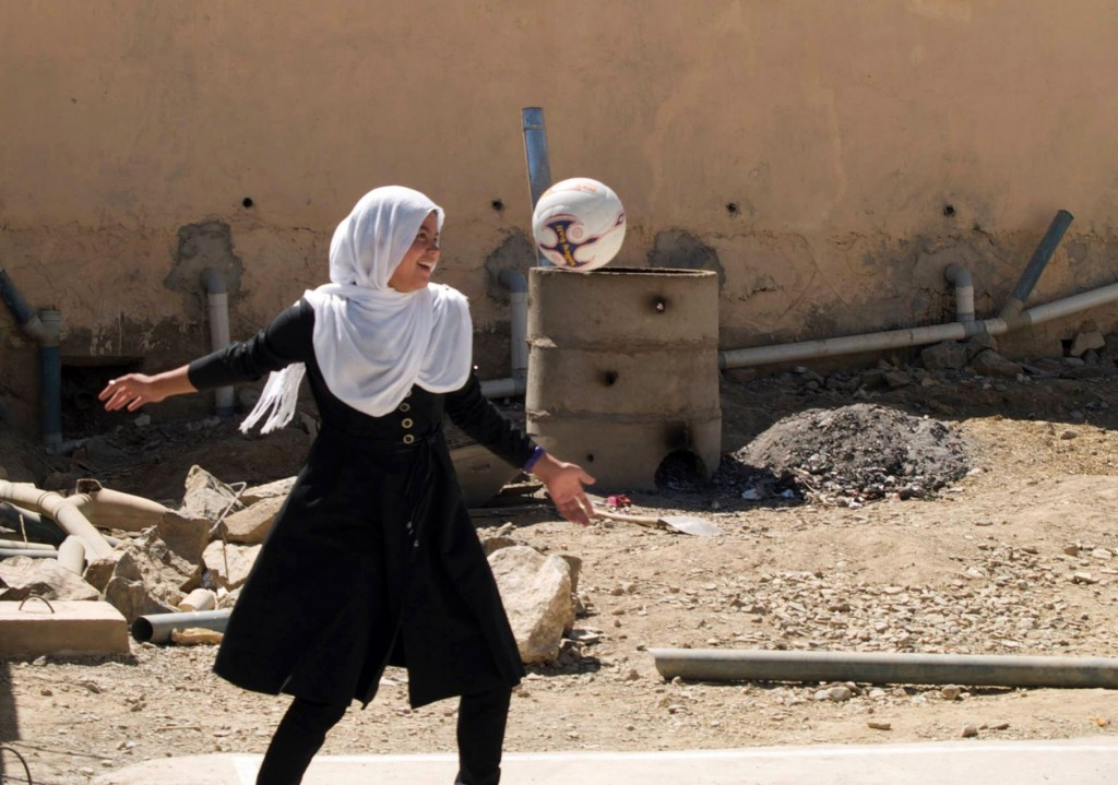 Young girl wearing a black dress and white head cloth plays with a soccer ball on a dusty footpath in Afghanistan