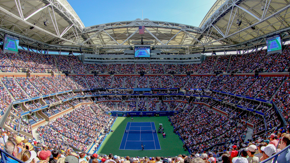 A panoramic shot of Arthur Ashe stadium at the U.S. Open. The shot shows the tennis court and the audience in the stands