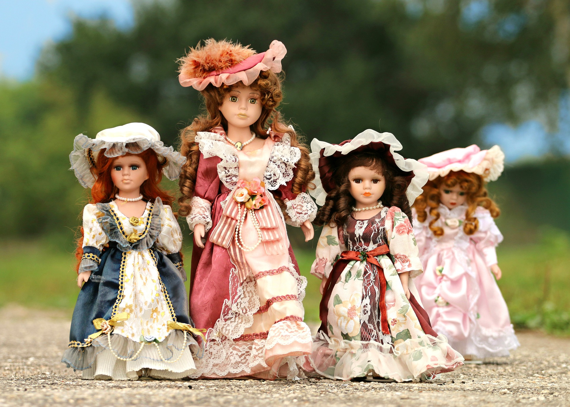 a set of dolls in 19th century clothes