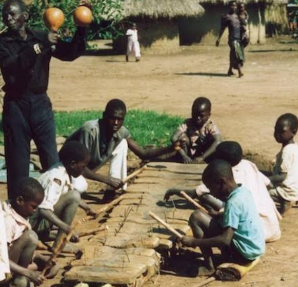 Children learning to play a musical instrument and the Griot guiding them