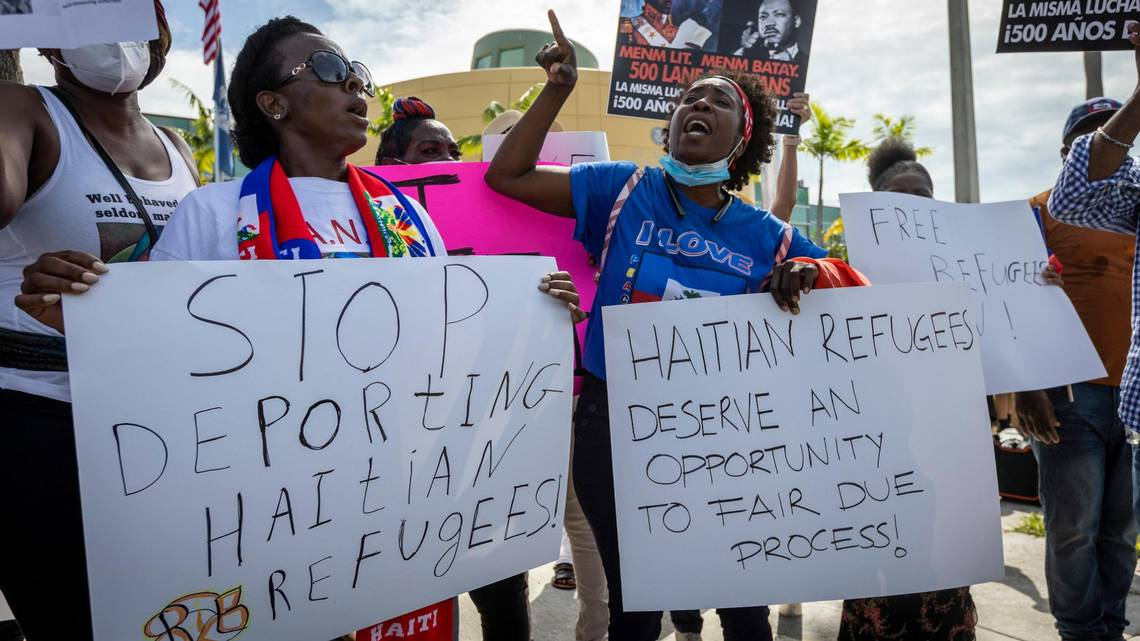 image of African women holding placards and protesting the deportations of Haitian immigrants