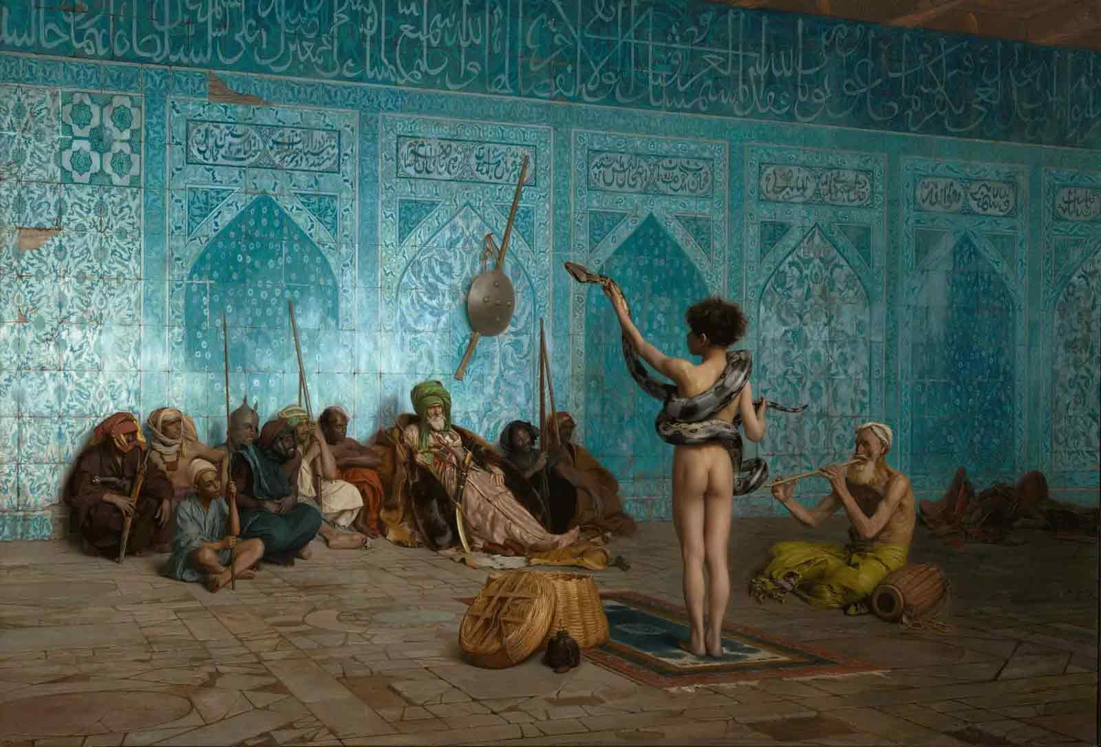 In an old Orientalist painting, a young boy stands with a snake draped over his arms and shoulders in front of an building that appears to be a Mosque