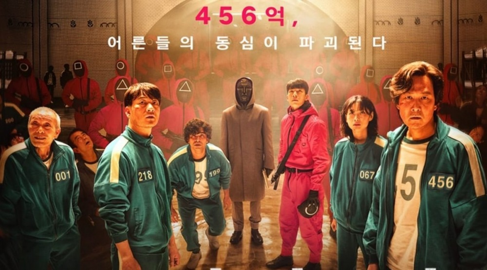 the poster of TV Series of Squid Game where the characters stand next to each other in track suits, while some in red and black clothes behind them masked people standing