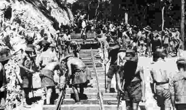 A black and white image of the early stages of building the railway, where POWs and Southeast Asian laborers are working hard in the sun, supervised by Korean and Japanese soldiers.