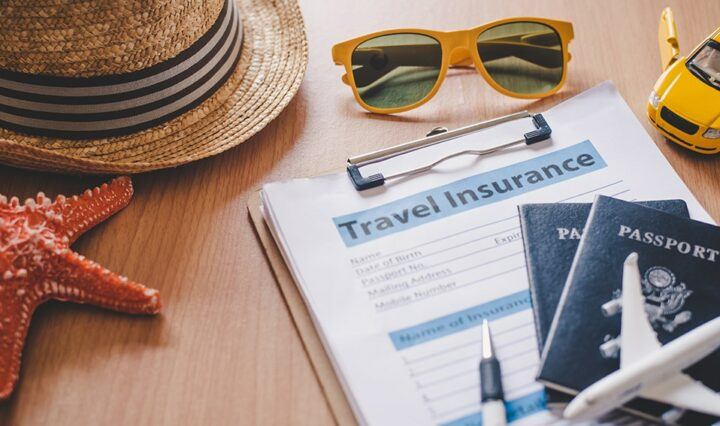 A table surface with a red starfish, a straw hat, orange sunglasses, two passports and a small toy areoplane, and a clipboard with a travel insurance form