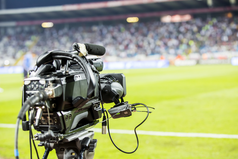 A television camera on the sidelines of a soccer field.
