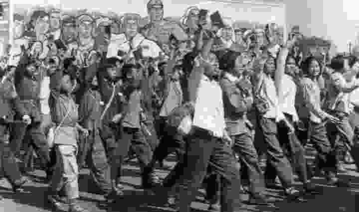A black and white images of Chinese students, marching, while wearing the red armbands around their arms during the Cultural Revolution.